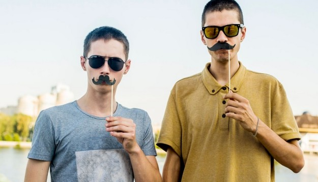 Two young men with fake moustaches. Movember for men's health.