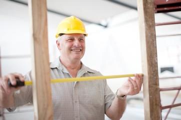 Builder measuring house frame